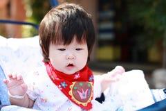 婴儿推车的愉快的女婴 免版税库存图片