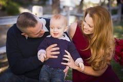 婴儿男孩和年轻军事父母戏剧在公园 免版税库存图片