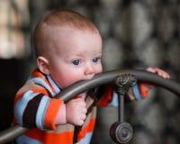 婴儿男孩蓝眼睛尖酸的锻铁床头板 库存照片
