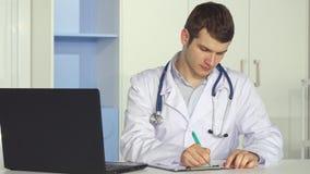 儿科医生在剪贴板写在办公室 免版税库存图片