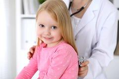 儿科医生在医院照顾婴孩 小女孩是由医生审查由听诊器 胳膊关心健康查出滞后 免版税图库摄影