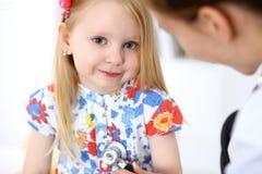 儿科医生在医院照顾婴孩 小女孩是由医生审查由听诊器 胳膊关心健康查出滞后 图库摄影