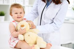 儿科医生在医院照顾婴孩 小女孩由有听诊器的医生审查 胳膊关心健康查出滞后 库存照片