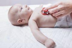 儿科医生审查有听诊器的新出生的男婴 免版税库存照片
