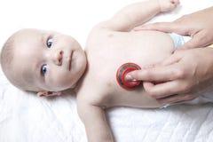 儿科医生审查有听诊器的新出生的男婴 免版税库存图片