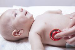 儿科医生审查有听诊器的新出生的男婴 免版税图库摄影