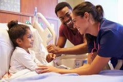 儿科医生参观的父亲和孩子在医院病床上 免版税库存图片