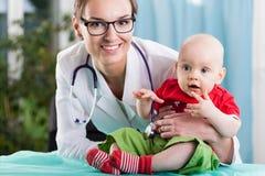 儿科医生和患者在医疗任命期间 免版税库存图片