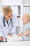 儿科医生在医院照顾婴孩 小女孩是由有听诊器的医生审查 胳膊关心健康查出滞后 免版税库存照片