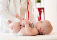 儿科医生审查五个月男婴 使用听诊器的医生听检查心跳的儿童胸口 免版税库存图片