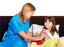 儿科医生被审查的小女孩 免版税库存照片