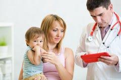 儿科医生医生审查的孩子 母亲 免版税库存照片