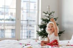 儿童、圣诞节和新年概念 可爱的白肤金发的女孩继续下去睡衣,与五颜六色的五彩纸屑的戏剧  免版税库存照片