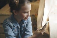 儿童、技术和通信概念-在家发短信在智能手机的微笑的女孩 免版税库存图片