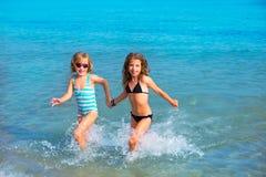 儿童一起运行在海滩岸的女朋友 免版税库存图片