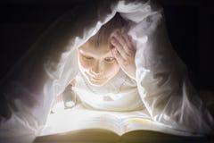 儿童上床时间 兄弟读一本书在有手电的一条毯子下 相当年轻男孩获得乐趣在儿童居室 免版税库存照片