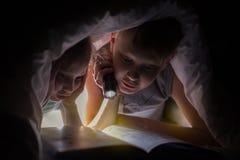 儿童上床时间 姐妹和兄弟读一本书在有手电的一条毯子下 免版税库存照片