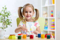 儿童与五颜六色的油漆的女孩绘画 库存图片