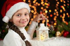 儿童与圣诞节装饰,与光,面孔表示和愉快的情感的黑暗的背景的女孩画象,在圣诞老人h穿戴了 免版税库存照片