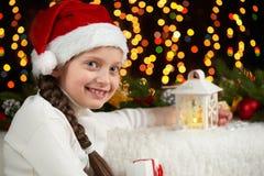 儿童与圣诞节装饰,与光,面孔表示和愉快的情感的黑暗的背景的女孩画象,在圣诞老人h穿戴了 库存图片
