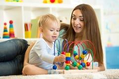 儿童与室内教育玩具的男孩戏剧 愉快 免版税库存照片