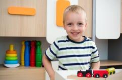 儿童与木火车的男孩戏剧在幼儿园 免版税库存照片