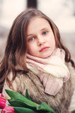 儿童与花的女孩画象在舒适温暖的室外冬天步行 免版税库存图片