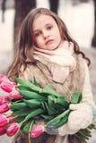 儿童与花的女孩画象在舒适温暖的室外冬天步行 免版税图库摄影