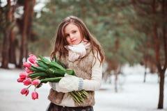 儿童与花的女孩画象在舒适温暖的室外冬天步行 免版税库存照片