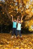 儿童五颜六色的秋天愉快的叶子户外 免版税库存图片