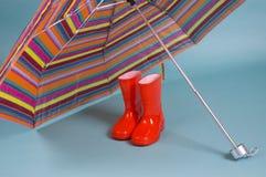儿童五颜六色的rainboots红色伞 库存图片