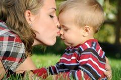 儿童亲吻母亲 库存图片