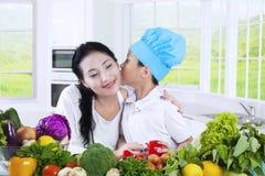 儿童亲吻他的妈妈,当烹调时 免版税库存照片