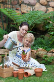 儿童从事园艺的母亲 免版税库存照片