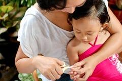 儿童剪切指甲盖母亲 库存图片