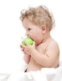 儿童卷发的画象吃绿色аpple 库存照片