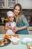 儿童厨房女孩烹调围裙杯形蛋糕曲奇饼小滑稽的三个姐妹盖帽奶油奶油装饰母亲妈妈匙子 库存照片