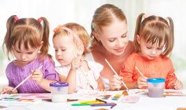 儿童双姐妹在幼儿园画与她的母亲的油漆 免版税库存照片