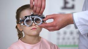 儿童反对和在寻找适当的屈光率的phoropter的医生改变的透镜 股票录像