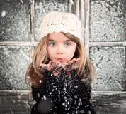 儿童吹的冬天雪花 免版税库存照片
