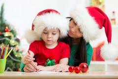 儿童和母亲文字给圣诞老人的圣诞节信件 免版税库存照片