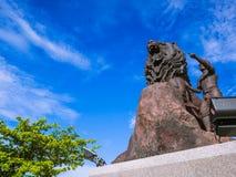 儿童和狮子雕象在公园 免版税图库摄影