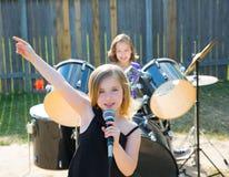 儿童唱歌歌手的女孩演奏活带在后院 免版税库存照片