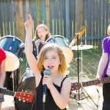 儿童唱歌歌手的女孩演奏活带在后院 库存图片