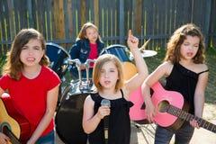 儿童唱歌歌手的女孩演奏活带在后院 库存照片