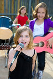 儿童唱歌歌手的女孩演奏活带在后院 免版税库存图片
