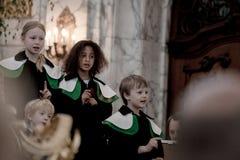 儿童唱诗班的成员在圣迈克尔教会唱歌 免版税库存图片