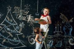 儿童圣诞节装饰结构树 兄弟和姐妹画在墙壁上的圣诞节歌曲 快活的圣诞节 库存图片