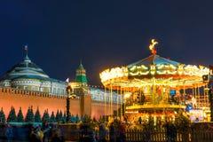儿童在克里姆林宫附近的` s转盘在莫斯科夜 免版税库存照片