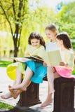 儿童在公园的阅读书 室外女孩坐反对树的和的湖 免版税图库摄影